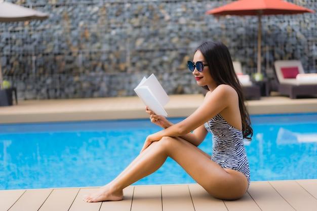 肖像画の美しいアジアの女性は屋外スイミングプールの周りの本を読む
