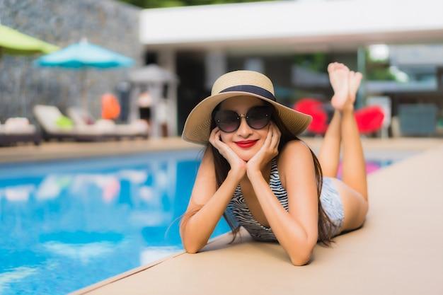 アジアの女性の美しい肖像画は、屋外スイミングプールの周りの幸せな笑顔をリラックスします。