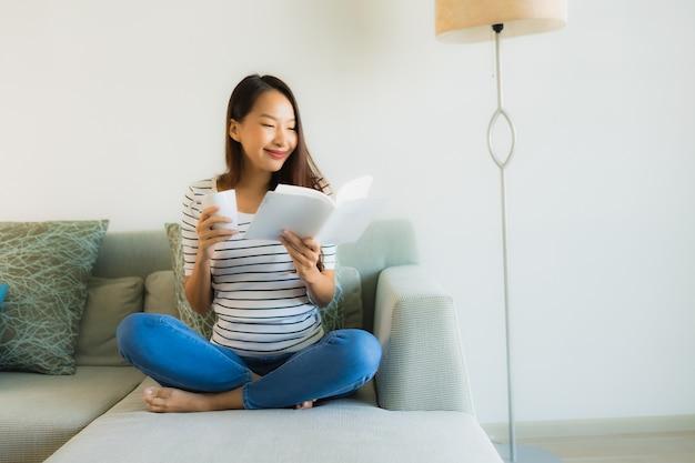コーヒーカップと本を読んで美しい若いアジア女性の肖像画