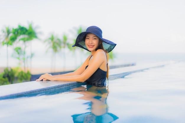 Улыбка красивых молодых азиатских женщин портрета счастливая ослабляет открытый бассейн в гостинице