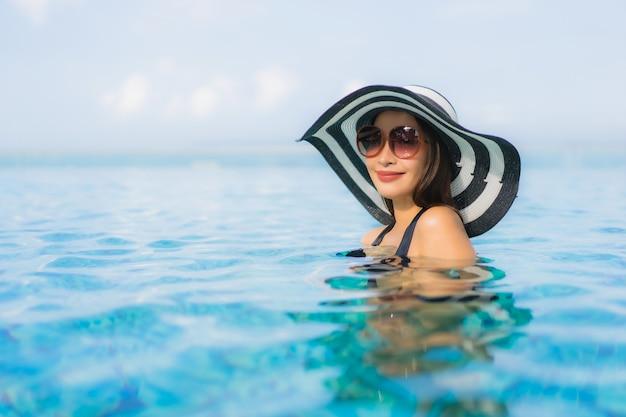 Улыбка красивых молодых азиатских женщин портрета счастливая ослабляет открытый бассейн в курорте