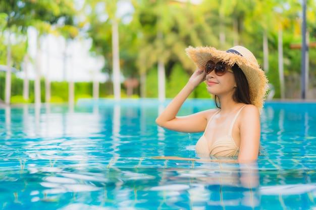 肖像画美しい若いアジア女性の幸せな笑顔はリゾートの屋外スイミングプールをリラックスします。