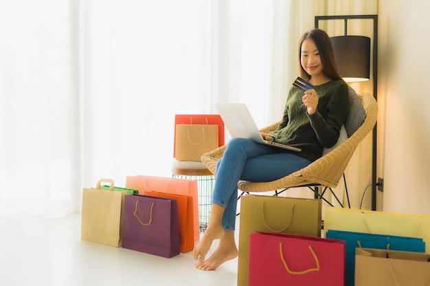 Женщины портрета красивые молодые азиатские используя компьтер-книжку компьютера с кредитной карточкой для онлайн покупок