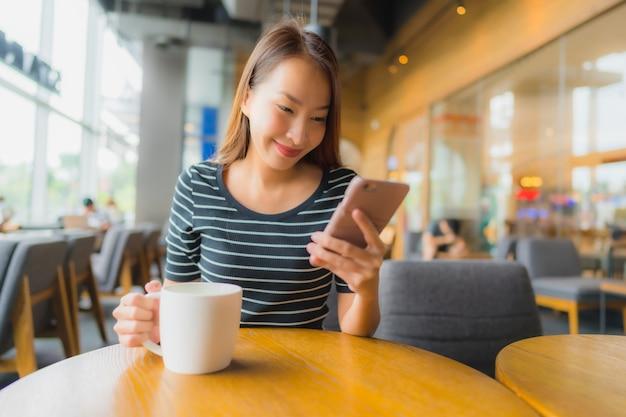 コーヒーショップカフェやレストランの携帯電話で美しい若いアジア女性の肖像画