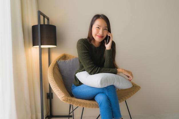 肖像画の美しい若いアジア女性の話携帯電話を使用して、ソファの椅子に座って