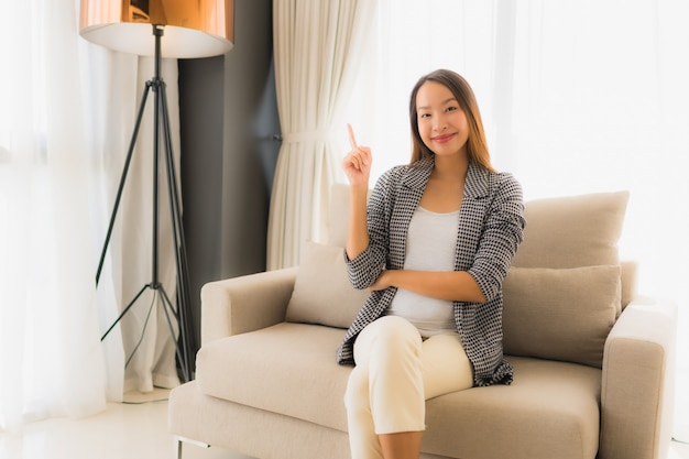 肖像画美しい若いアジア女性の幸せな笑顔はソファの椅子に座ってリラックスします。
