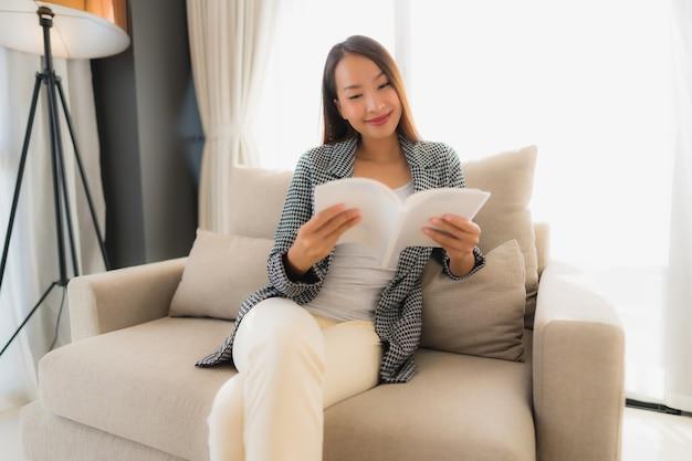肖像画本を読んで、ソファの椅子に座って美しい若いアジア女性