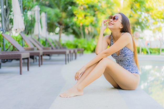 Улыбка красивых молодых азиатских женщин счастливая ослабляет вокруг открытого бассейна в курорте гостиницы