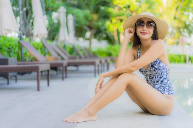 美しい若いアジア女性の幸せな笑顔は、ホテルリゾートの屋外スイミングプールの周りでリラックスします。