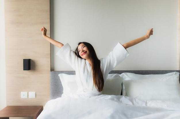 肖像画美しい若いアジア女性の幸せな笑顔はベッドでリラックス