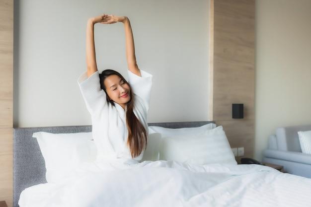 Улыбка красивых молодых азиатских женщин портрета счастливая ослабляет на кровати
