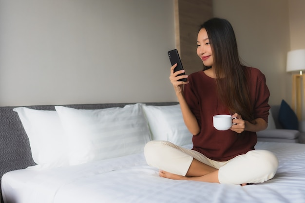 Улыбка красивых молодых азиатских женщин портрета счастливая с кофе и мобильным телефоном