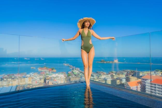 美しい若いアジア女性の幸せな笑顔は、休暇中の旅行のためのホテルリゾートの屋外スイミングプールの周りでリラックスします。