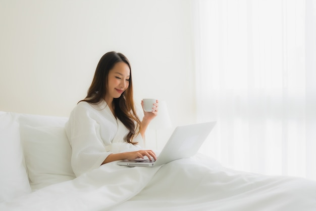 ベッドの上のコーヒーカップとコンピューターのラップトップを持つ美しい若いアジア女性の肖像画