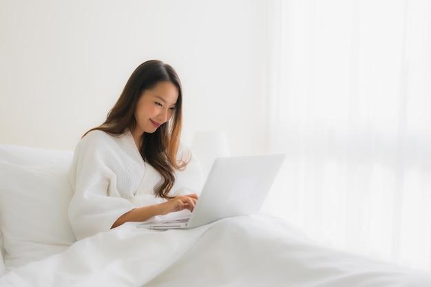 ベッドの上のコンピューターのラップトップで美しい若いアジア女性の肖像画