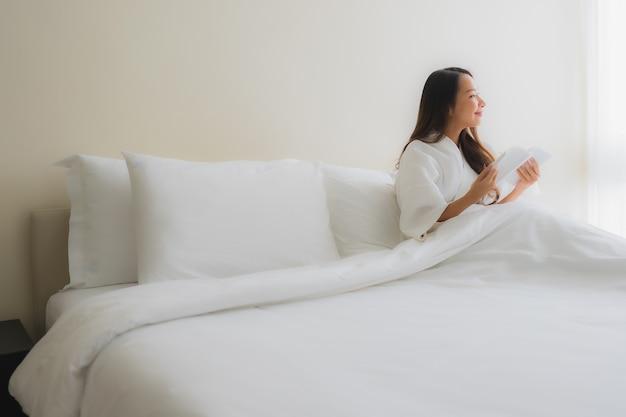 肖像画美しい若いアジア女性はベッドで本を読む