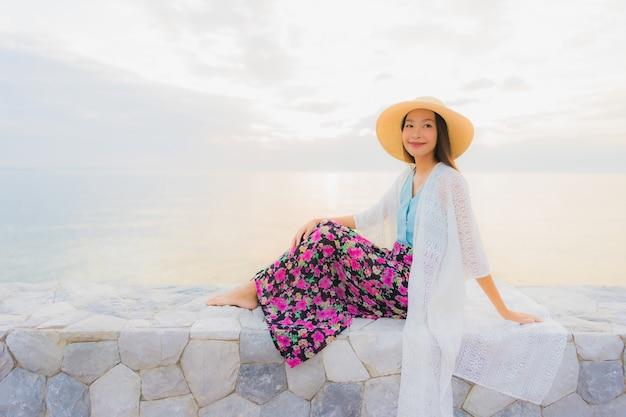 肖像画美しい若いアジア女性の幸せな笑顔海ビーチ海の周りでリラックスします。