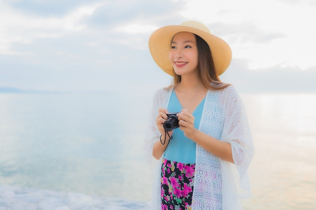 Улыбка красивых молодых азиатских женщин портрета счастливая ослабляет вокруг океана пляжа моря