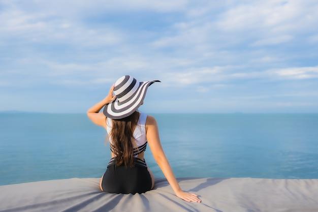 Женщина портрета красивая молодая азиатская вокруг океана пляжа моря