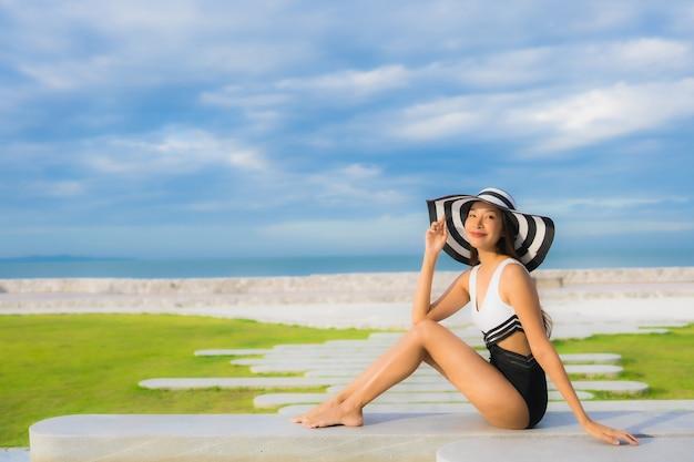 肖像画美しい若いアジア女性の幸せな笑顔はスイミングプールの周りでリラックスします。