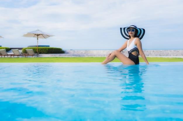 Улыбка красивых молодых азиатских женщин портрета счастливая ослабляет вокруг бассейна
