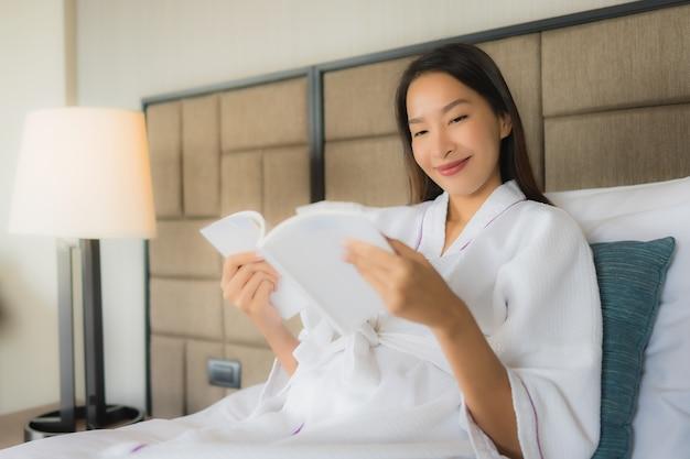 Женщины портрета красивые молодые азиатские с книгой на кровати