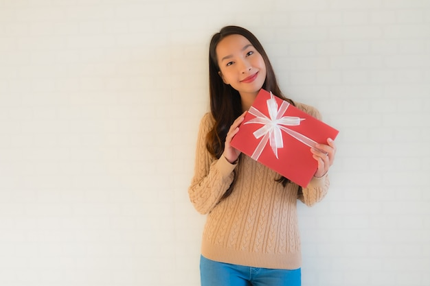 Улыбка красивой молодой азиатской женщины портрета счастливая с подарочной коробкой