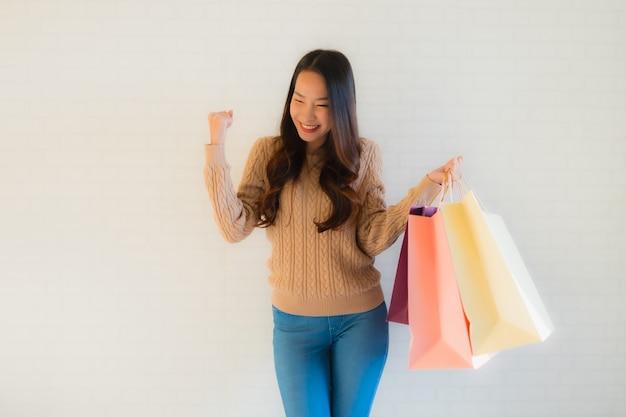 肖像画の美しい若いアジア女性の買い物袋と幸せな笑顔