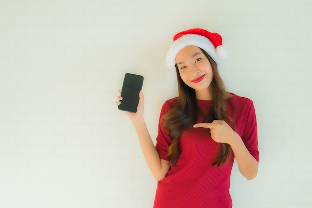 肖像画の美しい若いアジア女性は携帯電話でサンタのクリスマス帽子をかぶる