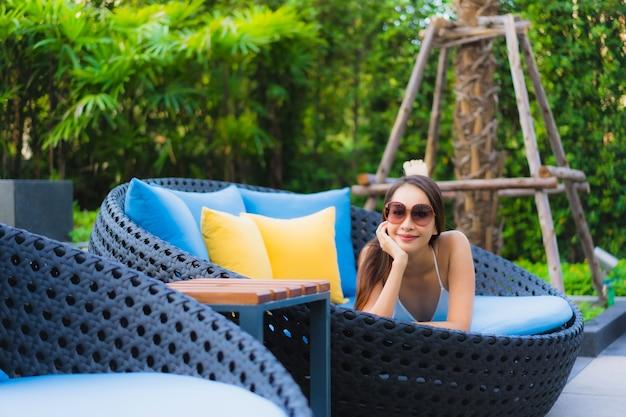 Улыбка красивой молодой азиатской женщины портрета счастливая ослабляет вокруг открытого бассейна