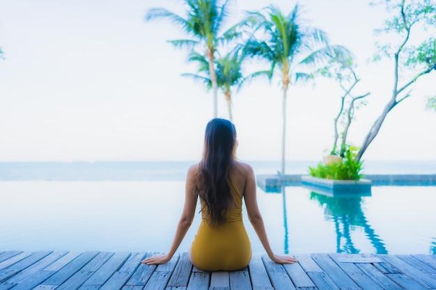 Улыбка красивых молодых азиатских женщин портрета счастливая ослабляет вокруг открытого бассейна