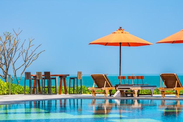 ホテルリゾートの屋外スイミングプール近くの海の周りの傘と椅子
