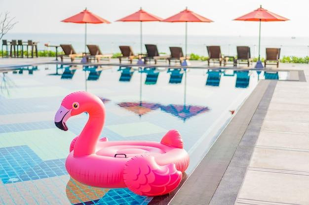 ホテルリゾートの傘と椅子のあるホテルリゾートのスイミングプールの周りのフラミンゴフロート