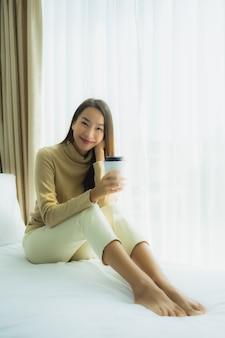 ベッドの上のコーヒーカップを持つ若いアジア女性