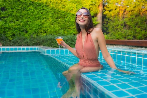 肖像若いアジア女性はホテルのスイミングプールの周りの幸せな笑顔をリラックスします。