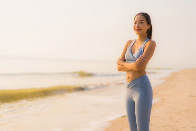 肖像画スポーツ若いアジア女性は運動を準備するか、ビーチ海海で実行
