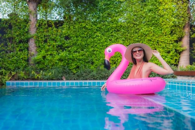 Женщина портрета молодая азиатская ослабляет счастливую улыбку вокруг бассейна в гостинице