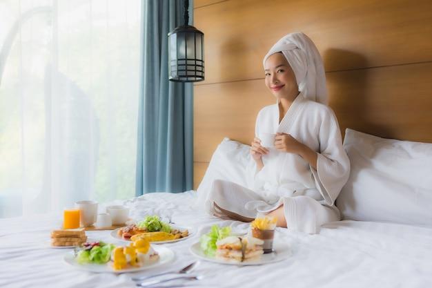 寝室で朝食とベッドの上の肖像若いアジア女性