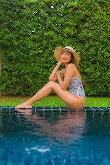 Улыбка молодой азиатской женщины портрета счастливая ослабляет вокруг открытого бассейна