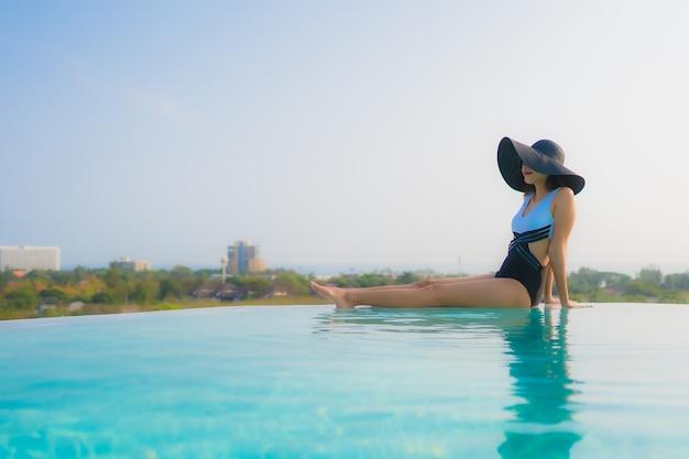Азиатская женщина отдыхает у бассейна
