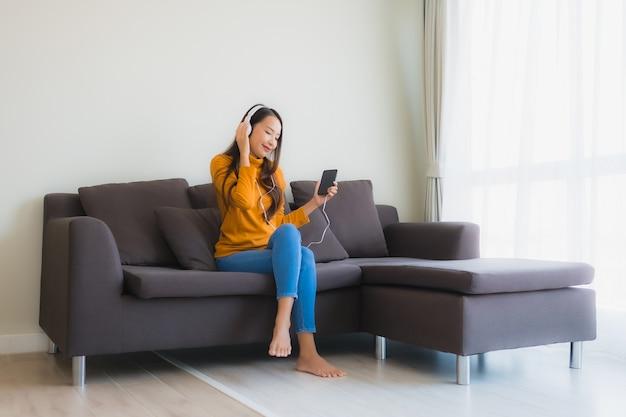 ソファで音楽を聴くためのイヤホンとスマートフォンを使用して若いアジア女性