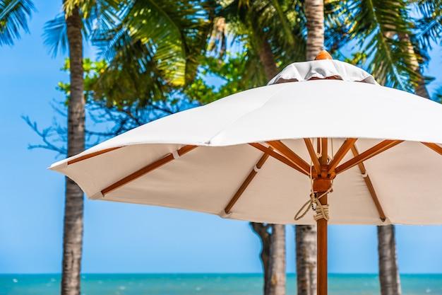 傘と豪華な屋外スイミングプールの周りの椅子が付いている空の海海の美しい風景