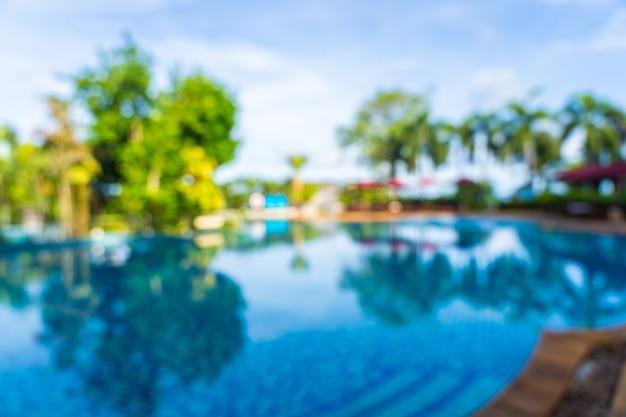 抽象的なぼかしとホテルリゾート、ぼやけた写真の背景の美しい屋外スイミングプールの焦点をぼかす