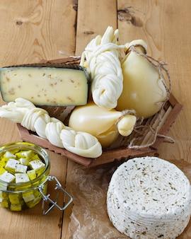 木製の背景にチーズの種類。