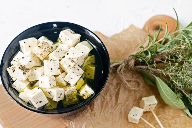 白い背景の上のスパイスと木の板のプレートにフェタチーズのマリネ