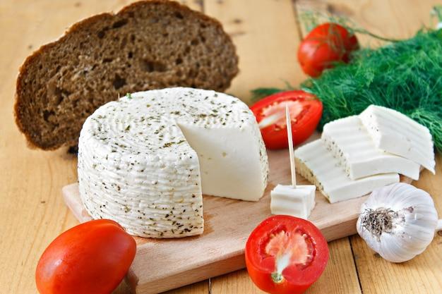 ホワイトチーズ、パン、トマト、ニンニク、木製の背景