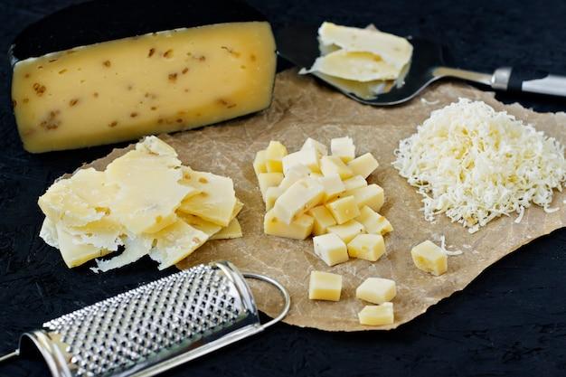 カチョッタチーズ、おろし金とナイフで黒い背景にスライス