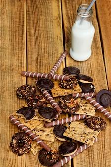 Молоко с печеньем в стеклянной бутылке на деревянном фоне