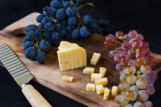 黒の背景にブドウと木の板にカチョッタチーズ