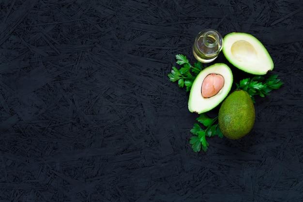 Авокадо, лимонная петрушка, растительное масло, оливковое масло, масло авокадо на черном фоне.